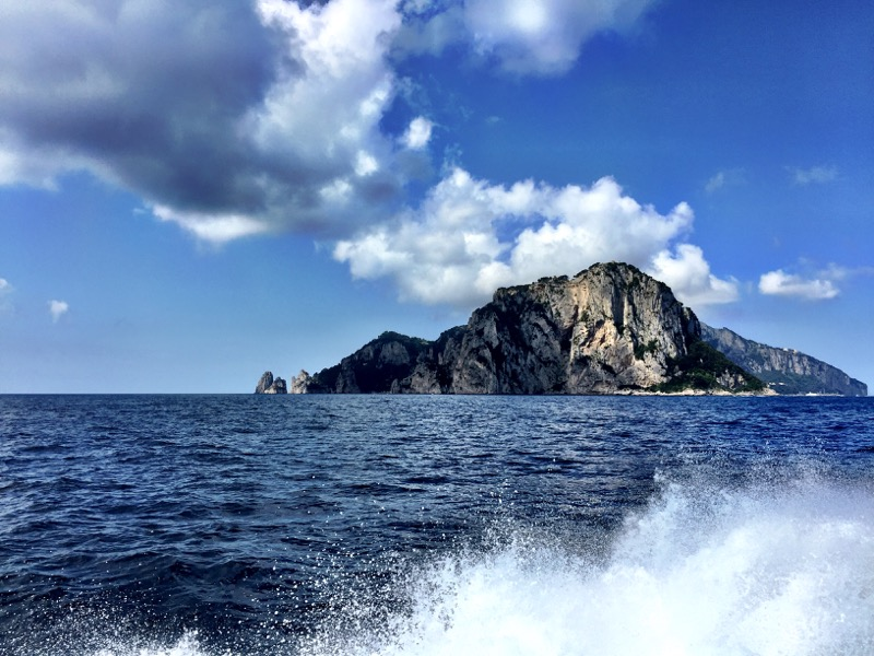 Approaching the Isle of Capri from Positano. I Faraglione is seen at the left of the island.