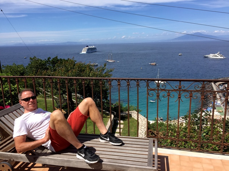 Clint enjoying the sites and sounds of Capri's Marina Grande from our Airbnb balcony