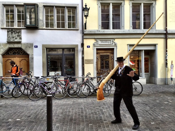 One of the alpine horn blowers taking his horn and splitting